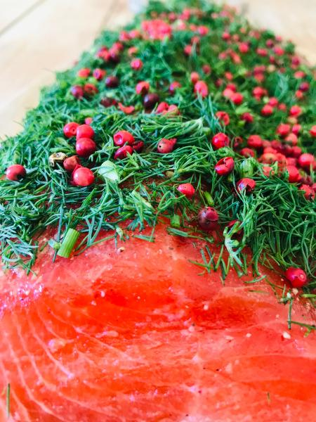 Stained (graved) salmon trout with fresh dill and pink berries